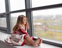 Lite slogg sig in flickan i slags tvåsittssoffa stucken filt och sammanträde på en fönsteravsats som ser till och med exponerings Royaltyfri Bild