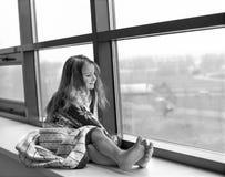 Lite slogg sig in flickan i slags tvåsittssoffa stucken filt och sammanträde på en fönsteravsats som ser till och med exponerings Arkivfoto