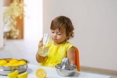 Lite smakar flickan i en gul klänning den lagade mat lemonaden arkivbild