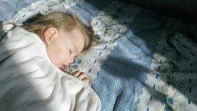 Lite sover flickan med blont hår på sängen och tänt av solljus arkivfilmer