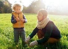 Lite spelar den blonda pojken och hans mamma utanför arkivbild