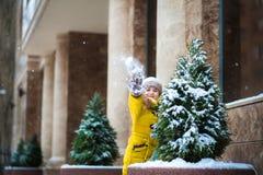 Lite spelar flickan i ett gult omslag med insnöat vintern Barnet döljer bak en julgran, och kast snöar på kammen Royaltyfri Fotografi
