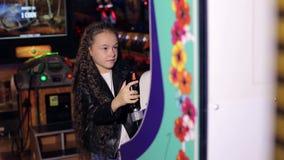 Lite spelar flickan med långt lockigt hår videospel i moderna barns rum stock video