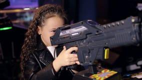 Lite spelar flickan med långt lockigt hår videospel i moderna barns rum arkivfilmer