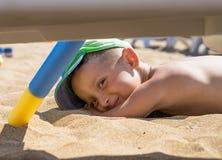 Lite spelar pojken i sanden på havet, de lilla benen och fingrarna, i en baddräkt, en bakgrund av havsgulingsand och blått w Arkivfoton