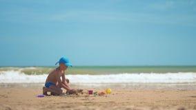 Lite spelar pojken i sanden på havet, de lilla benen och fingrarna, en bakgrund av gul sand för havet och blått vatten stock video