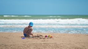 Lite spelar pojken i sanden p? havet, de lilla benen och fingrarna, en bakgrund av gul sand f?r havet och bl?tt vatten arkivfilmer