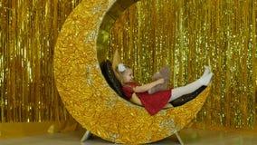 Lite spelas flickan i en röd klänning med en nallebjörn Flickan sitter på landskapet av månen stock video