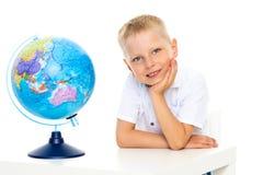 Lite studerar pojken geografi på ett jordklot arkivfoton