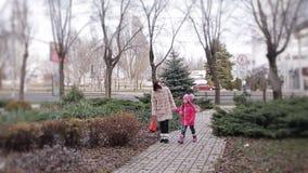 Lite talar flickan med hennes moder glatt, när han går på en vinterstad lager videofilmer
