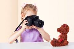 Lite tar flickan bilder av en leksakbjörn royaltyfri foto