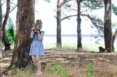 Lite tar flickan med en retro kamera bilder i skogen, Arkivfoton
