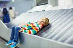 Lite trött ungepojke på flygplatsen som reser Royaltyfri Foto