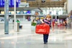 Lite trött ungepojke på flygplatsen som reser royaltyfri bild