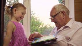Lite två-år-gamla flickalekar med hennes farfar arkivfilmer
