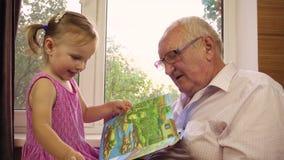 Lite två-år-gamla flickalekar med hennes farfar lager videofilmer