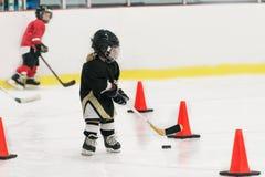 Lite utbildar den gulliga hockeyflickan på is Flickan bär oavkortad hockeyutrustning: hjälmen handskar, åker skridskor pinne puck arkivbild