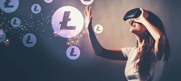 Litecoin при женщина используя шлемофон виртуальной реальности стоковая фотография rf
