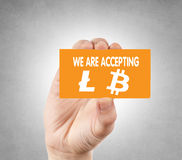 Litecoin and bitcoin. We are accepting litecoins and bitcoins calling card in the hand royalty free stock photo