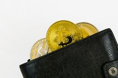 Litecoin, bitcoin and ethereum lie in black leather wallet closeup. Silver litecoin, golden bitcoin and silver ethereum  lie in black leather wallet closeup  on Royalty Free Stock Images