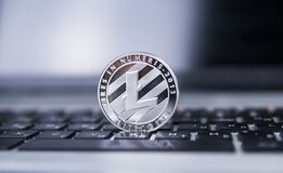 Litecoin coin on a laptop in centre of the frame. Litecoins crypto currency on a laptop black keyboard. Digital currency. Litecoin coin on a laptop. Litecoins stock photography