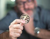Litecoin cryptocurrency in hand of a casual businessman Stock Image