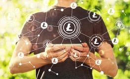 Litecoin med mannen som rymmer hans smartphone fotografering för bildbyråer