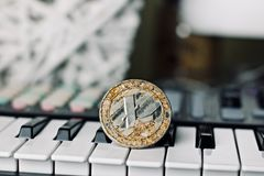 Litecoin and music keyboard. Digital currency physical metal litecoin coin and music keyboard. Cryptocurrency music concept royalty free stock photography