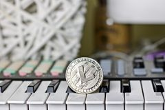 Litecoin and music keyboard. Digital currency physical metal litecoin coin and music keyboard. Cryptocurrency music concept royalty free stock image