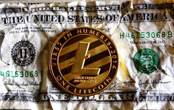 Litecoin one crushed  dollar. Litecoin on Crushed dollar banknote.  Cryptocurrency conspiracy  concept Royalty Free Stock Image