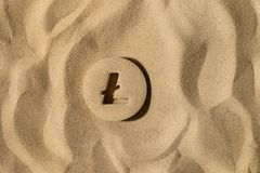 Litecoin Symbol Under the Sand stock images