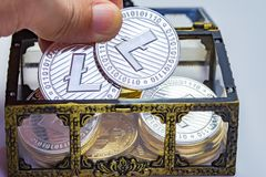 Litecoin Treasure Chest. Close up of a hand picking out a Litecoin coin from a treasure chest Stock Images