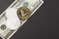 Litecoins, bitcoin и 100 долларов на черном камне шифера Стоковое фото RF