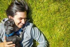 Liten älsklings- hund och hans ägare som har roligt utomhus Royaltyfri Fotografi