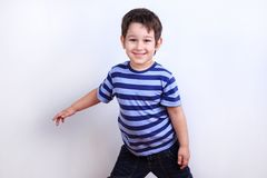 Liten älskvärd pojke som ler och poserar, studiofors på vit Emo arkivfoto