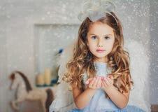 Liten ängel i ljus - blå klänning som blåser snö Fotografering för Bildbyråer