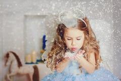 Liten ängel i ljus - blå klänning som blåser snö Arkivfoton