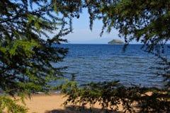 Liten ö i fjärden av Lake Baikal till och med träden arkivbild