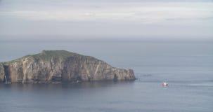 Liten ö i mitt av havet med vattnet i stillhet och ett skepp som ankras nära det arkivfilmer