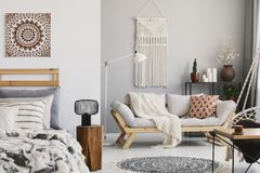 Liten öppet utrymmelägenhet som är inre med den beigea soffan med kudden, makramé på väggen, kugge med stearinljus och växter och arkivfoton