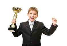 Liten affärsman med lyckligt göra en gest för guld- kopp royaltyfria bilder