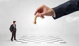 Liten affärsman som spelar schack med ett begrepp för stor hand fotografering för bildbyråer