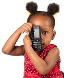 Liten afrikansk amerikanflickagyckel med telefonen Arkivfoto