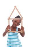 Liten afrikansk flicka som rymmer en husform - svarta människor Arkivbild