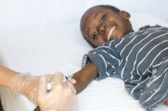 Liten afrikansk pojke som får visarinjektionen från den vita sjuksköterskan Woman royaltyfri foto