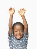 Liten afrikansk pojke som rymmer hans händer upp i luftstunden som skrattar och ler fotografering för bildbyråer