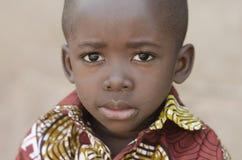 Liten afrikansvartpojke som ser ledsen på kameran arkivfoton
