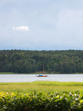 Liten ankrade segelbåten på en lugna flod under en lynnig sky Arkivfoto