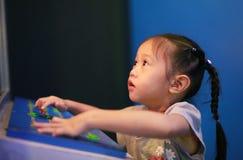 Liten asiatisk barnflicka för närbild som spelar gallerivideospelet arkivbilder