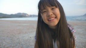 Liten asiatisk barnplockning beskjuter på stranden stock video
